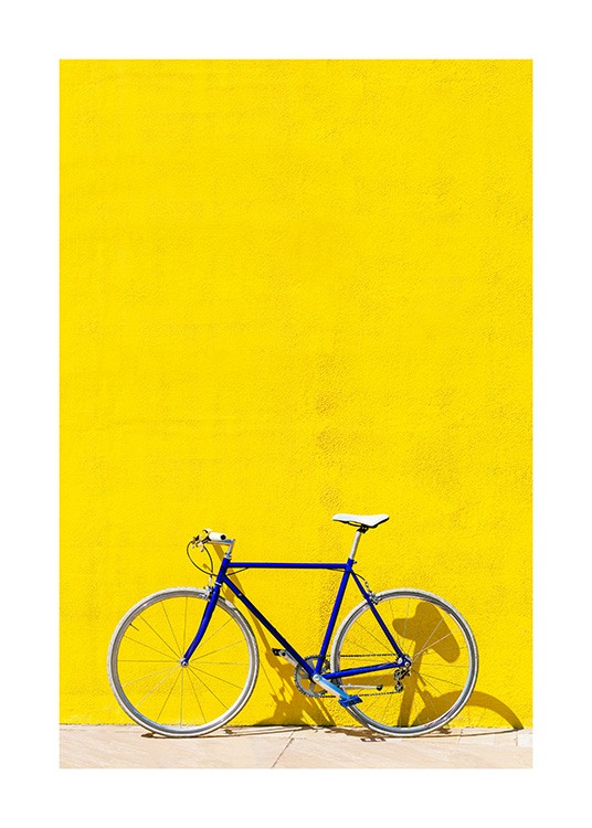 Bicicleta azul de pie delante de una pared de color amarillo brillante