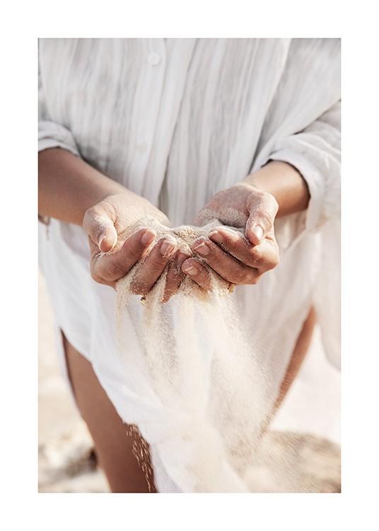 – Fotografía de las manos llenas de arena de una mujer que lleva una camisa de lino blanca.